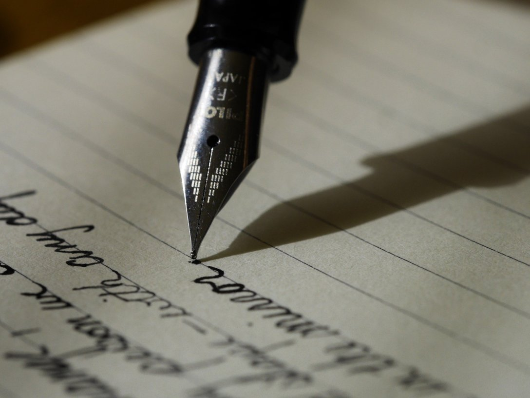 Fountain pen point on lined paper with lines in cursive handwriting