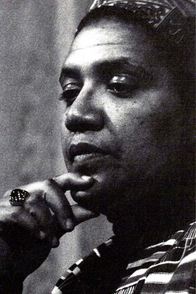 Closeup of Audre Lorde wearing a patterned turban, kente scarf, and jeweled ring and holding her chin with the thumb and forefinger of her right hand